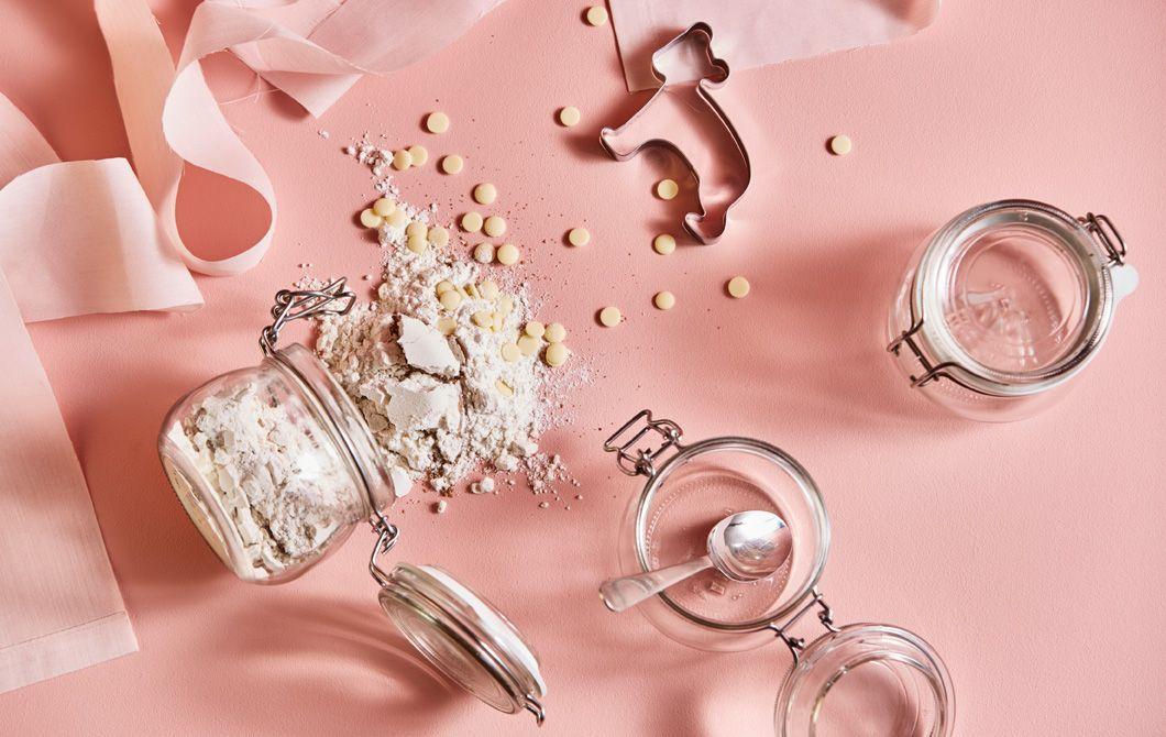 Ingredienser til cookies samt krukker og kakeformer mot en rosa bakgrunn, sett ovenfra.