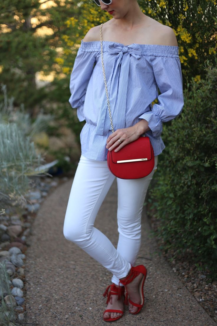 ruffled blue off the shoulder shirt + white skinny jeans + red cross body purse + red lace up sandals.  This cute summer outfit is the perfect red, white, and blue outfit for Labor Day, Memorial Day, or the 4th of July outfit.  Featured on Dresses And Denim Fashion Blog .  Get the outfit details here: http://www.dressesanddenim.com/red-white-blue-outfit/