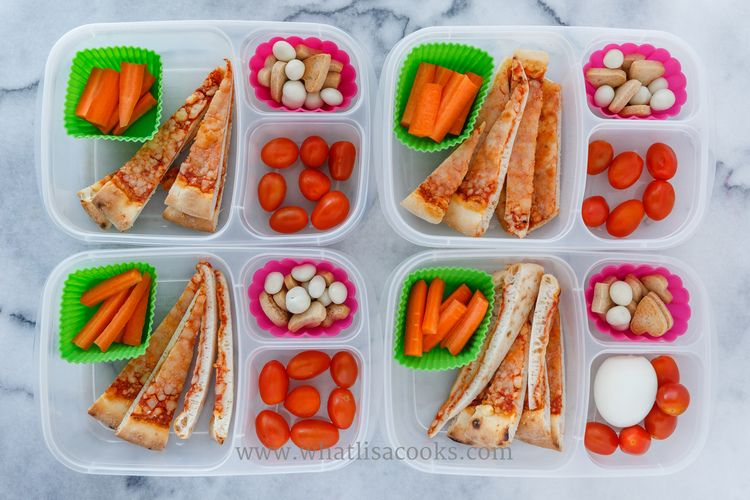 Leftover cheese pizza, cut into strips so it's a little easier to eat, with tomatoes, carrots, yogurt raisins, and a few homemade sugar cookies. One child also got a boiled egg. Packed in  Easy Lunchboxes , with  square silicone baking cups.