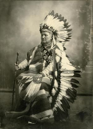 Studio photograph of Pleasant Porter who was the Chief of the Creek Nation. He is wearing a Plains Indian feather bonnet. The photograph was taken prior to December 8, 1904.
