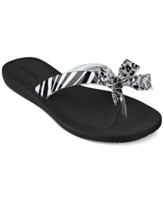 4410a842f5cf26 Guess dresses up the classic flip flop with a decorative bow for a sweet  touch.