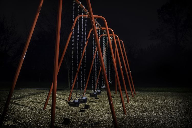 Swing Set Shot At Night Light Source Is A Tall Parking Lot