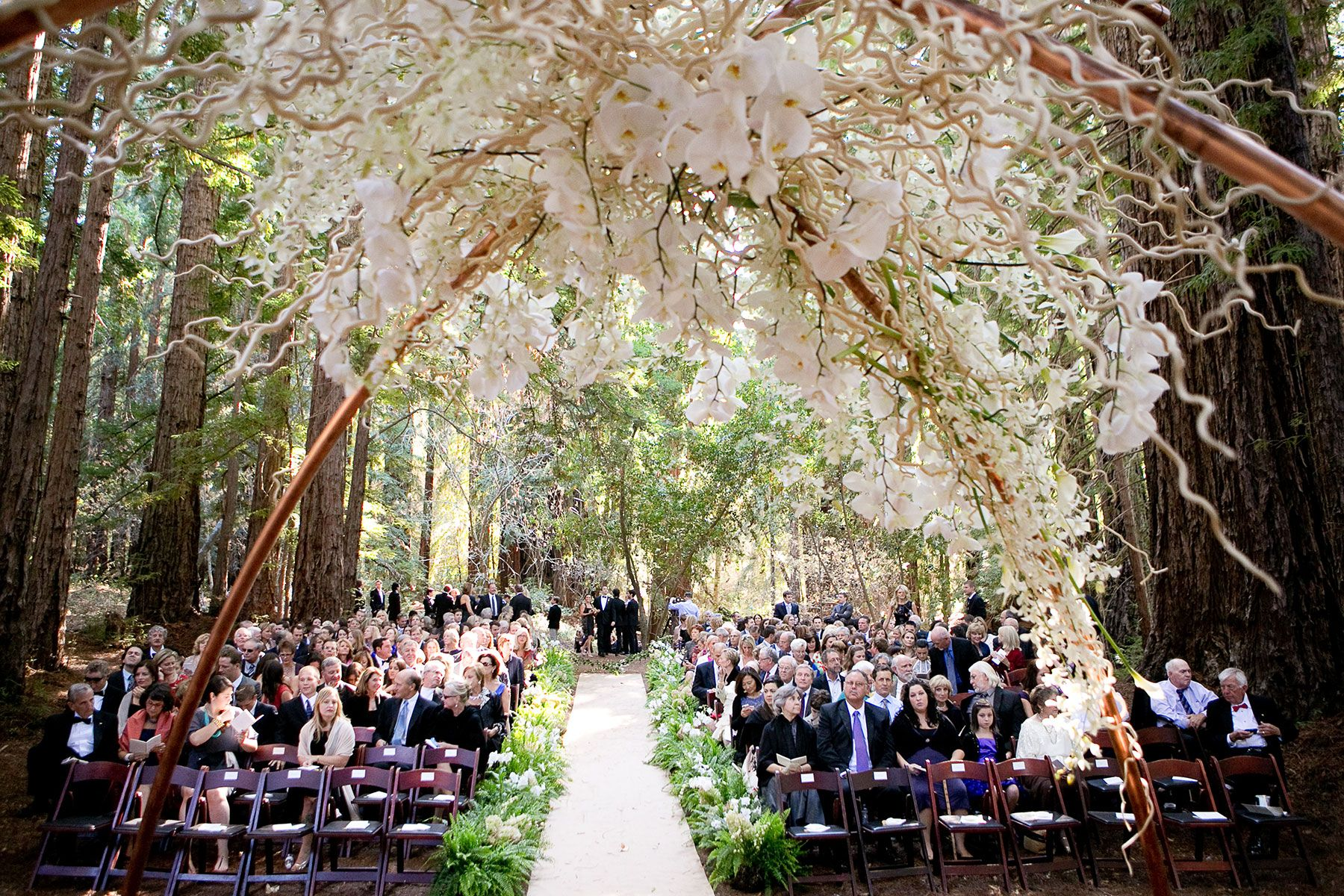 Modern copper ceremony arch with white orchids and branches. Design by Waterlily Pond Studio www.waterlilypond.... Santa Lucia Preserve, Carmel Valley. Larissa Cleveland Photography.