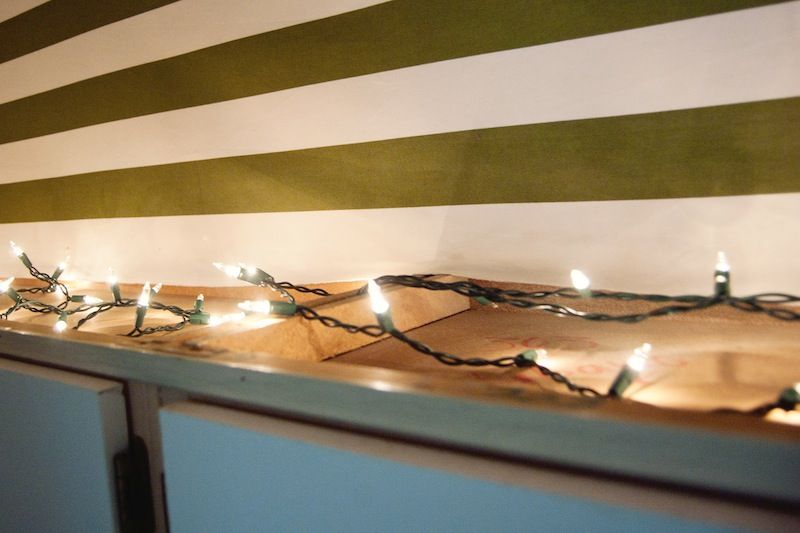 Use strand of christmas lights to provide lighting above kitchen