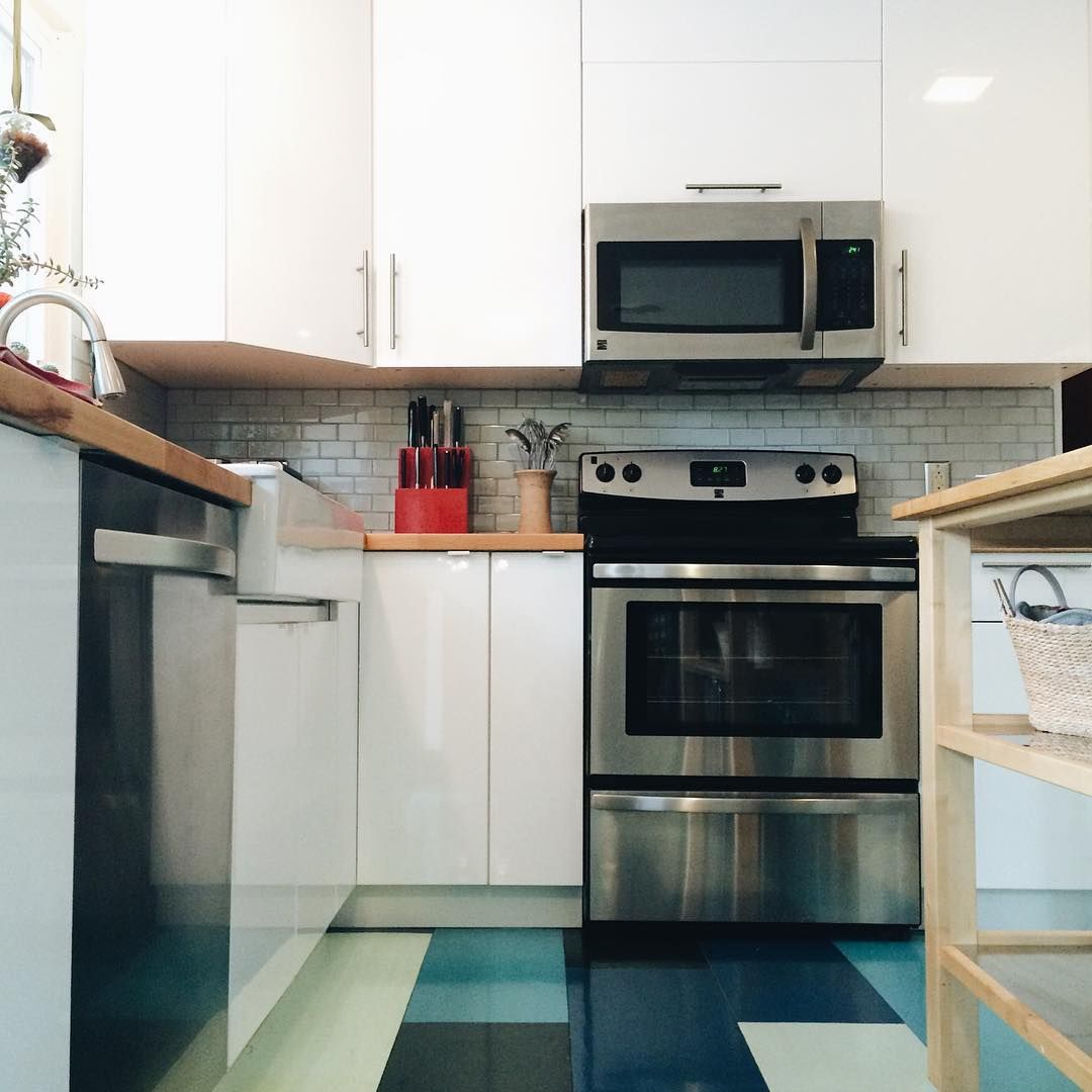 """A shot of the kitchen from yesterday's open house...because it was such a unique home. The cabinets are Ikea. The floors were a DIY: plywood """"tiles"""" epoxied in various shades of blue. So clever and colorful! #housecreeper"""