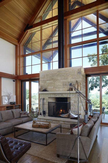A timber frame bent houses large glass panels creating ...