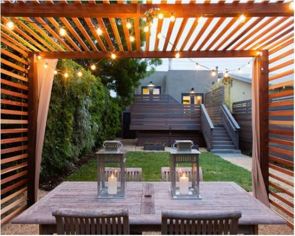 Pergola dining area with draperies and lights hanging from above
