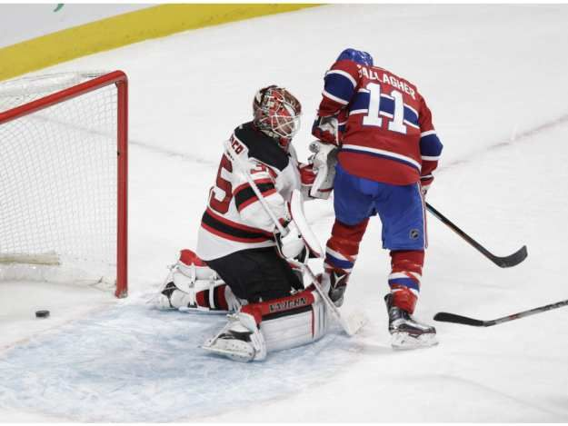 Jan.06 2016 - NJ 1 - Mtl 2 - The puck goes through the pads of Devils goalie Cory Schneider on a goal by captain Max Pacioretty, while Schneider is being crowded by Brendan Gallagher during the first period at the Bell Centre on Wednesday.