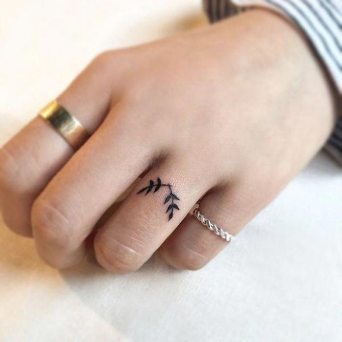 Kleines schwarzes Tattoo am Ringfinger, goldener und silberner Ring #fingertattoos #Tattoosonneck