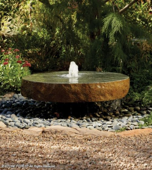 love this simple bubbler fountain  and also how it is tucked into a space with plants behind it