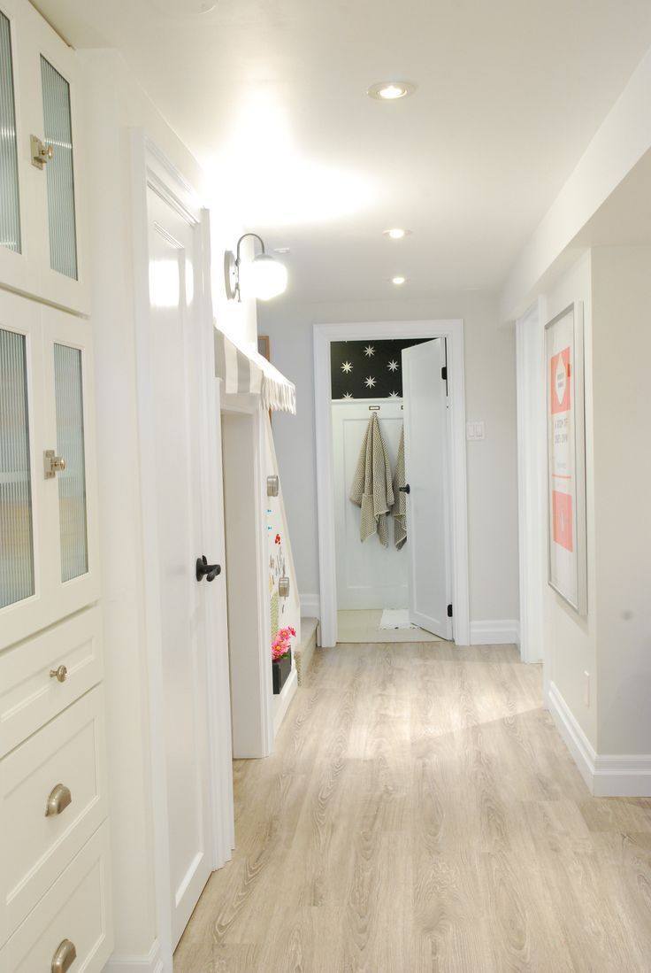 bright white basement with light wood floors white cabinetry ...