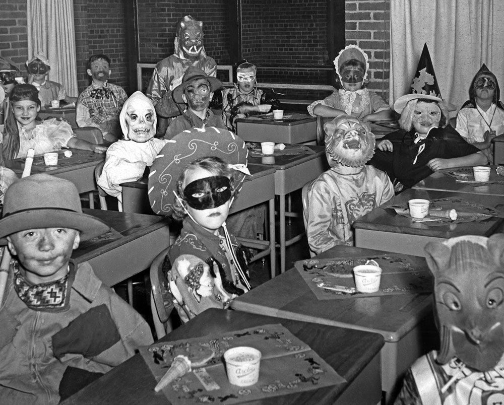 Third grade students dressed in costume and seated at desks during ...