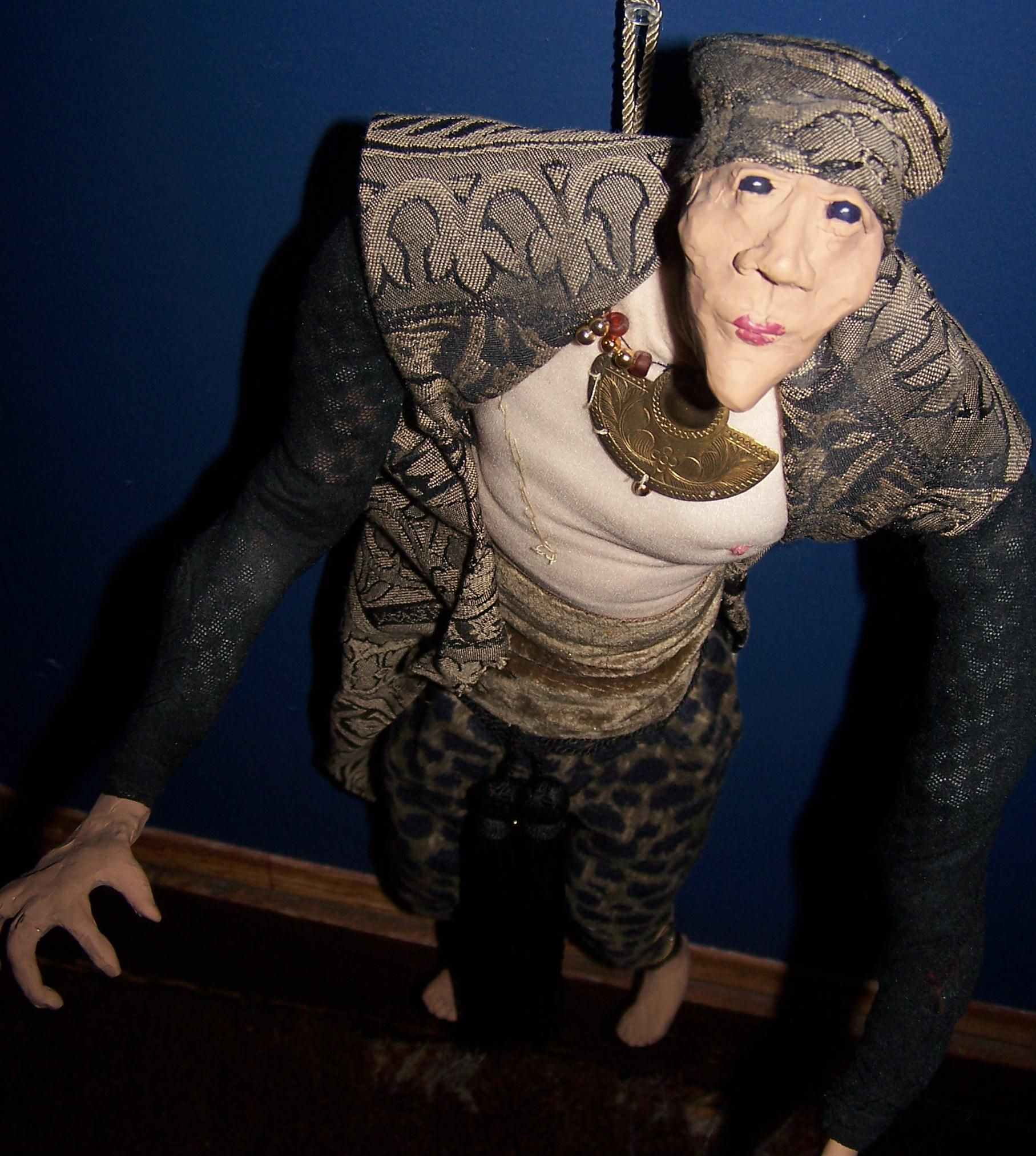 "This is another of my ""Amazon Now"" sculptures. Hand-sculpted face, hands and feet. Fabric over a wire armature with primitive stitches over her chest where a breast once was."
