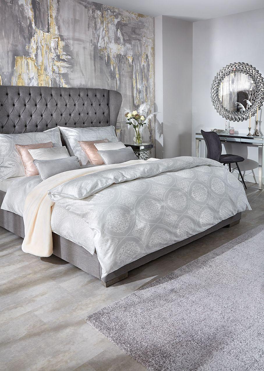 Graues Bett mit hoher Kopfleiste und glamourösen Accessoires #trendybedroom