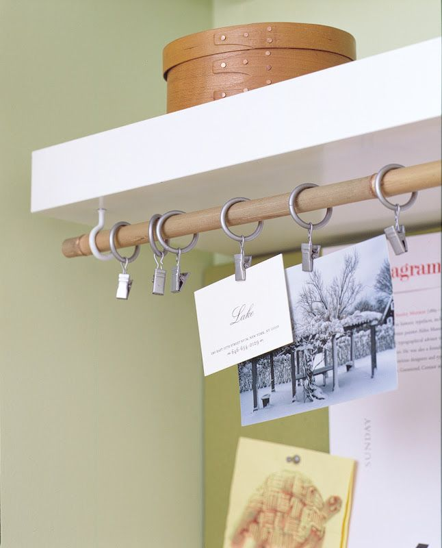Here, cup hooks and a drapery rod function as a place to display photos and business cards. This would be a great way to group fabrics sort of a hanging Idea board