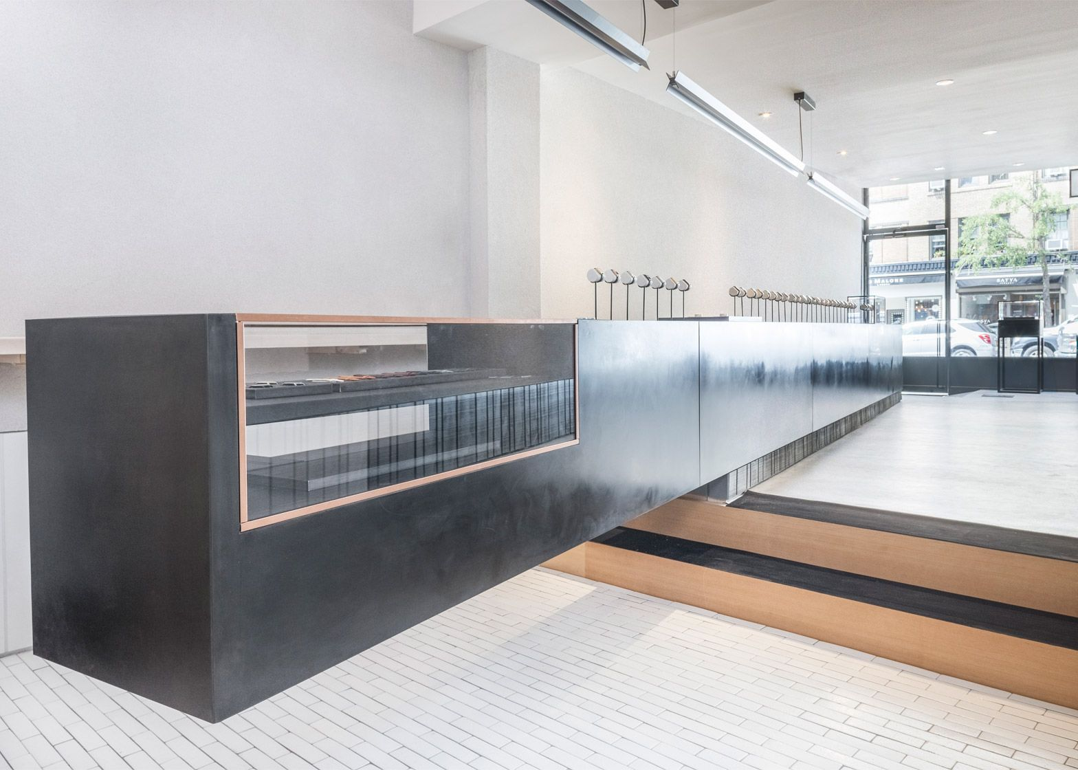 London creative agency Studio Mills has completed a Manhattan store for online watch brand Larsson & Jennings, featuring a cantilevered display counter and a bar serving typical Swedish refreshments.