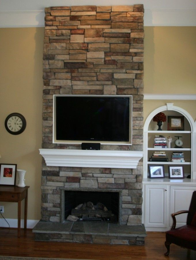 Amazing Stone Fireplace Designs With Mantels : Amazing Stacked Stone Fireplace Design With White Mantel And Wall Mounted LCD TV Along With White Book Cabinets Also Wooden Table And Brown Leather Armchairs Along With Wooden Floor