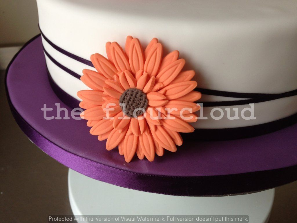 Orange flowers on this simple elegant birthday cake Celebration