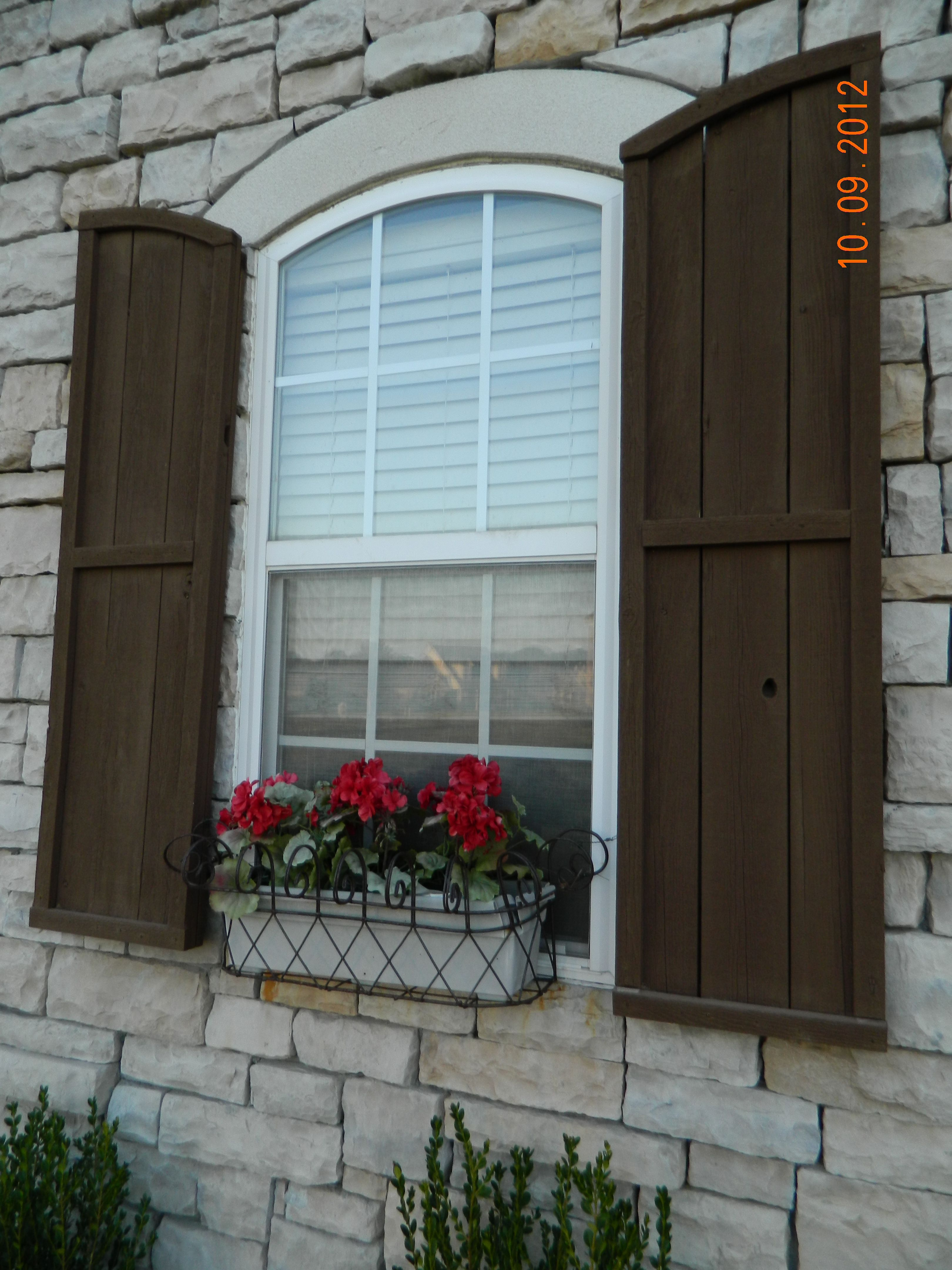 Window design for house exterior  arches made of stucco blend well with the stone walls wooden