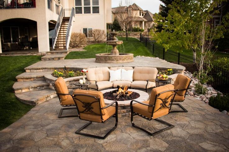 The terraced garden provides plenty of spaces for outdoor entertaining. A formal stone water fountain provides a focal point and leads visitors to the larger entertaining area with a cozy outdoor fire pit. Ample seating ensures a comfortable spot for everyone to relax on this luxurious stone patio.