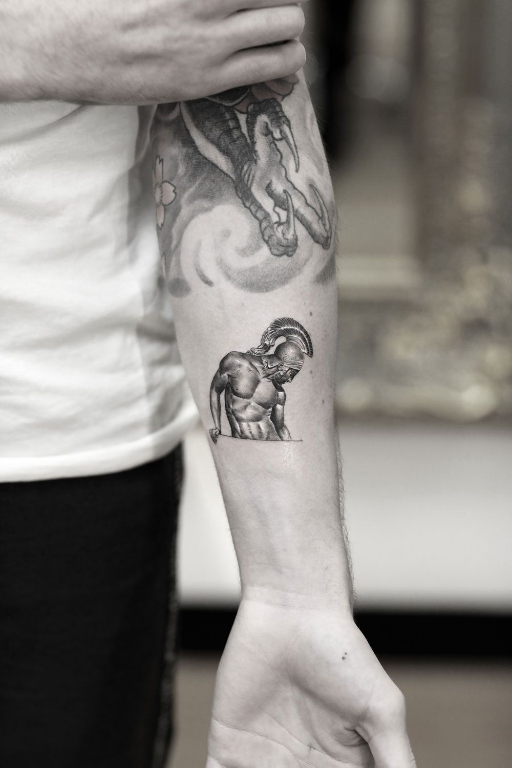 This is a Single Needle tattoo of a statue created by