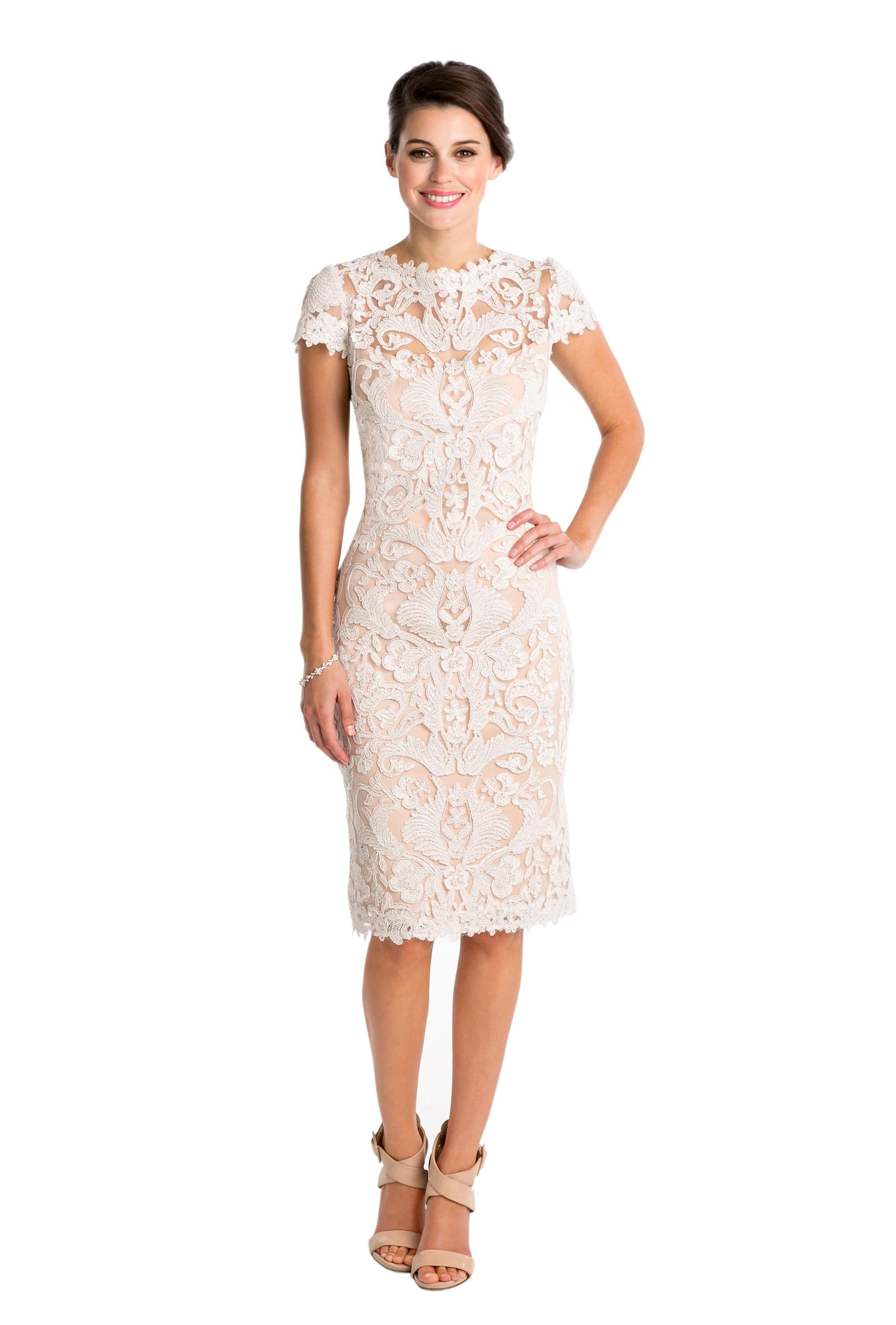 A short lace dress with ivory lace over a petal sheath and