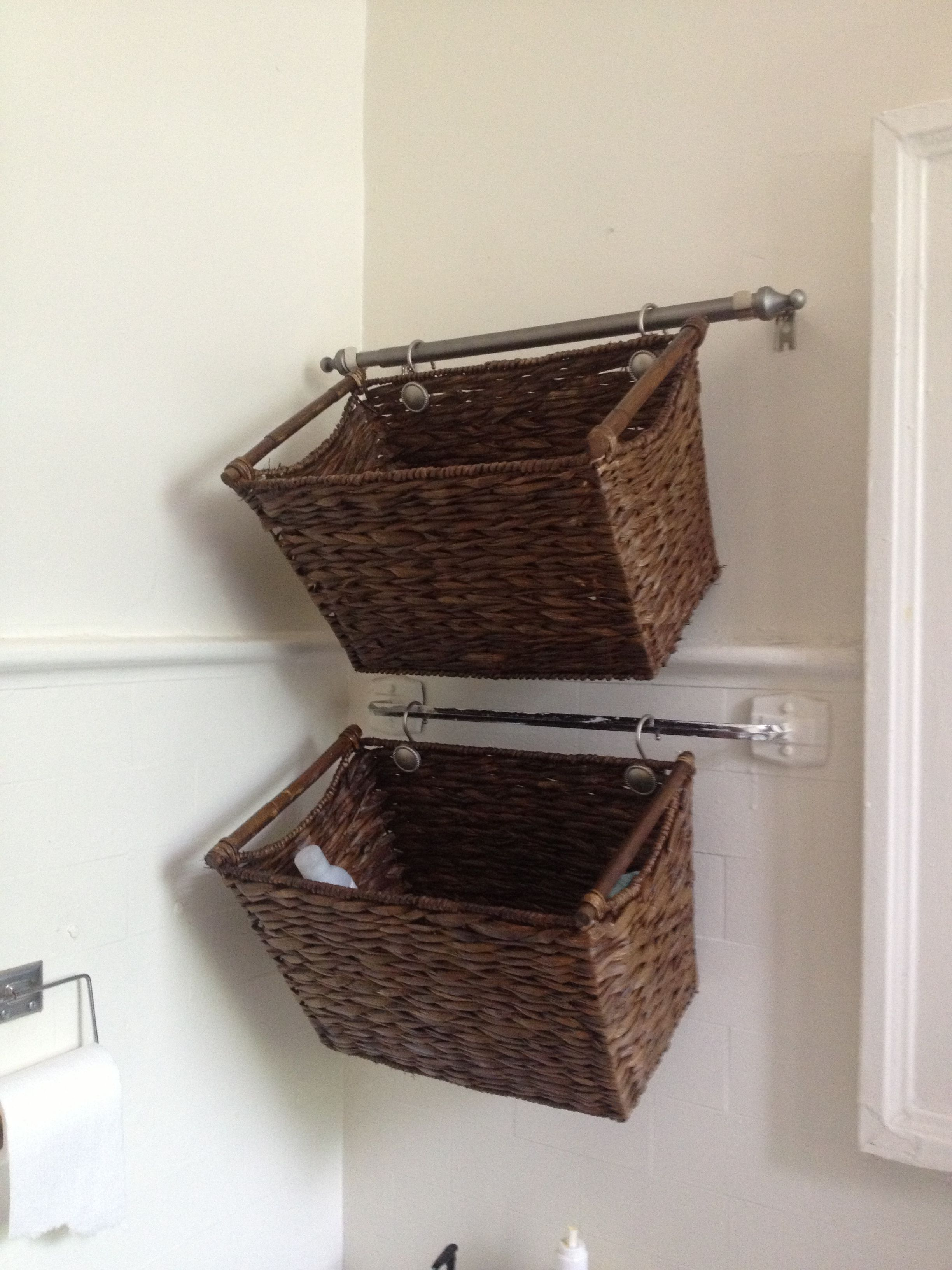 Cut down a curtain rod and hang wicker baskets for cute u easy