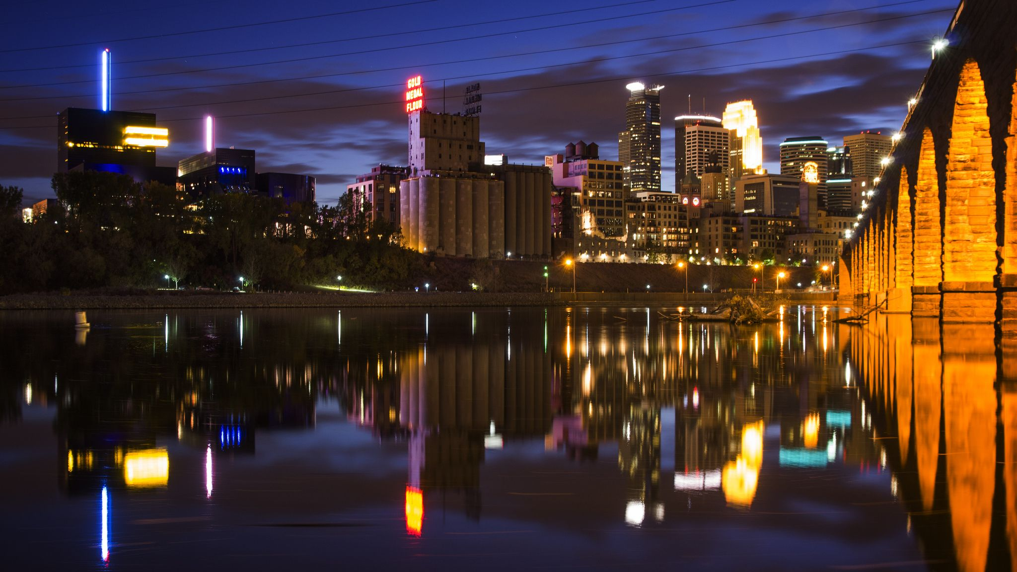 Downtown Minneapolis At Night And The Stone Arch Bridge Over The