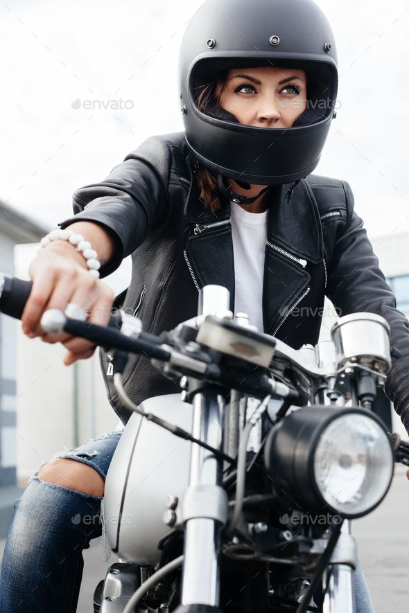 Biker woman in leather jacket on motorcycle love her handles on the handlebars, …