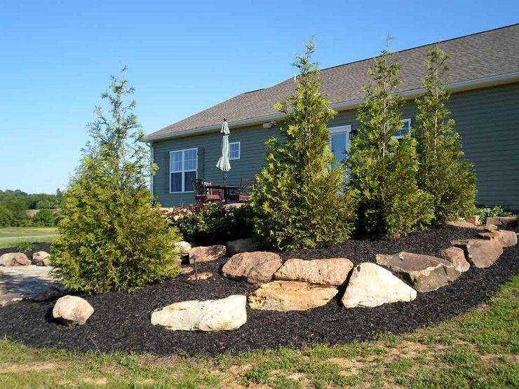 berm boulders and mulch in backyard