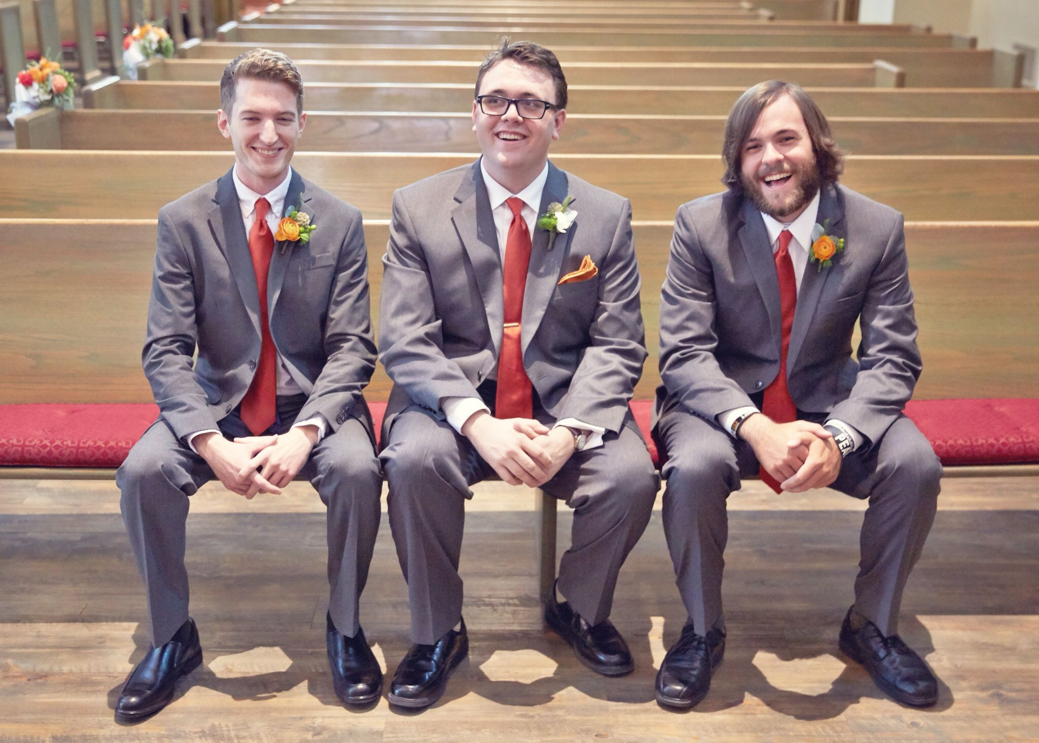 Grey suits with Spanish orange ties and fresh boutonnières for indoor July wedding.