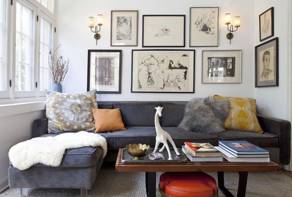 grey couch, orange accents, black and white prints on the wall.