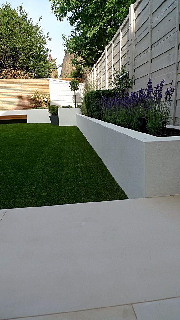White planters with purple flowers lavender against grass for Modern grasses landscaping