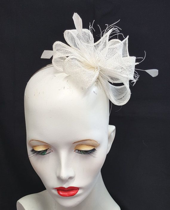 This fascinator is in a very pale ivory almost white with rolled edge sinamay loops and a smattering of feathers. This is mounted onto a metal headband and is designed primarily to be worn to the left side of the head Handmade by me in the UK Any questions please ask I am always happy to help