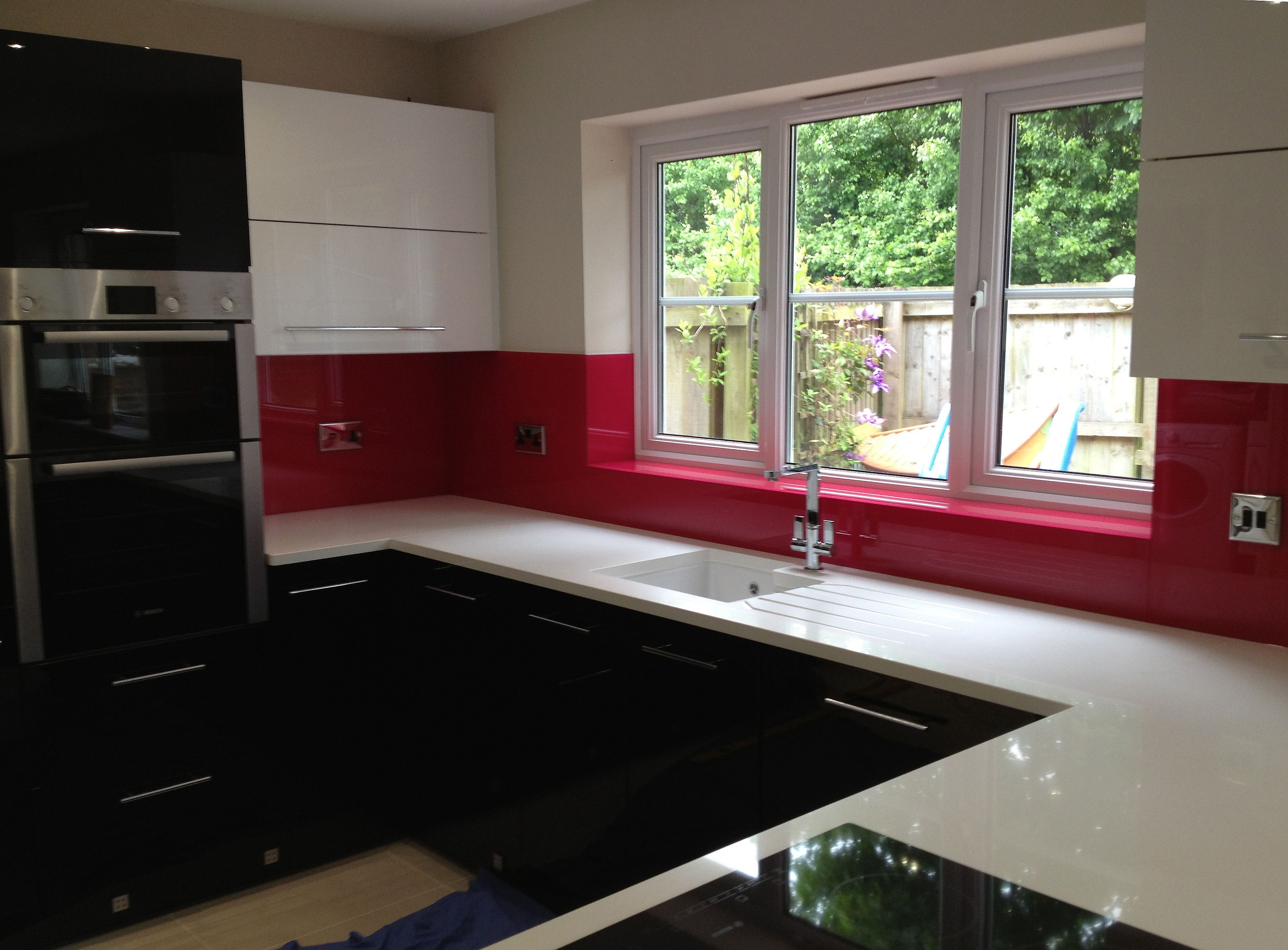 Lovely cherry red glass splashback fitted by easy glass splashbacks showing a glass window sill Kitchen profile glass design