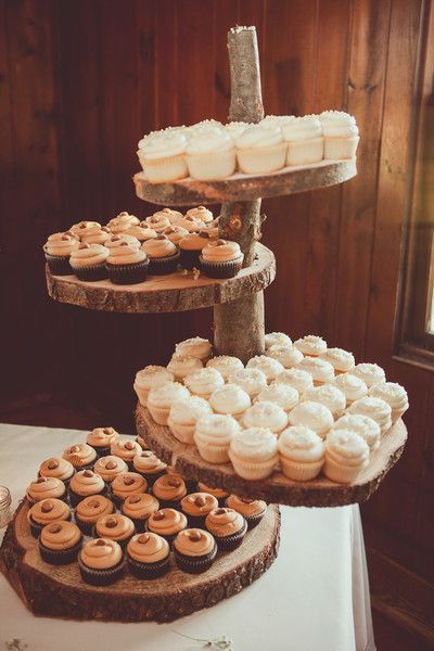 A variety of frosted cupcakes displayed on a wooden tree slice cake display were also served. Venue/Caterer: Columbia Ballroom