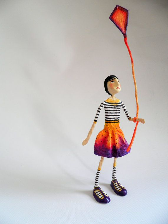 This sculpture of a little girl playing with a kite is a unique piece. About 13 inches tall. Its made by cartapesta technique, by the superposition of paper and glue layers, some parts are made of air dry clay and string. Hand painted with acrylics.