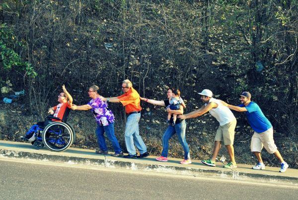 Familia impulsando a su familias en silla de ruedas