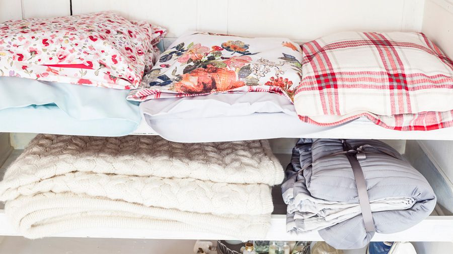 Colourful bed linen stored in pillow cases and folded blankets | Quick and easy laundry tips and hacks | Tesco Living