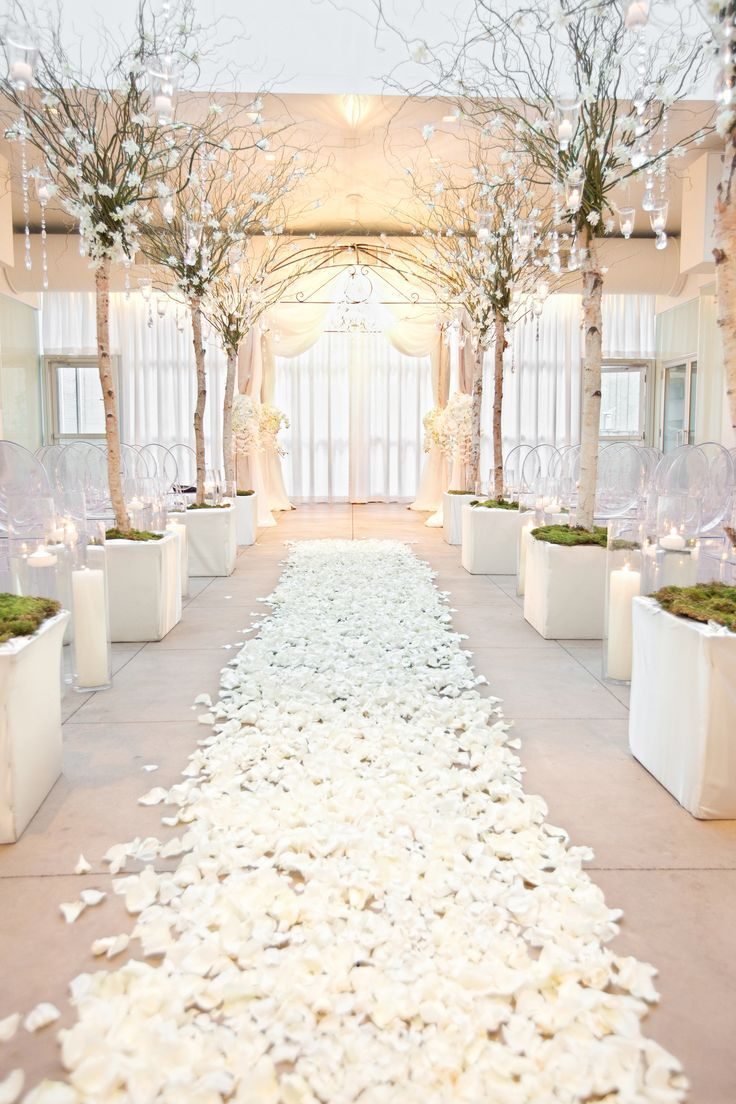 An aisle of white rose petals and branches dripping with crystals ...