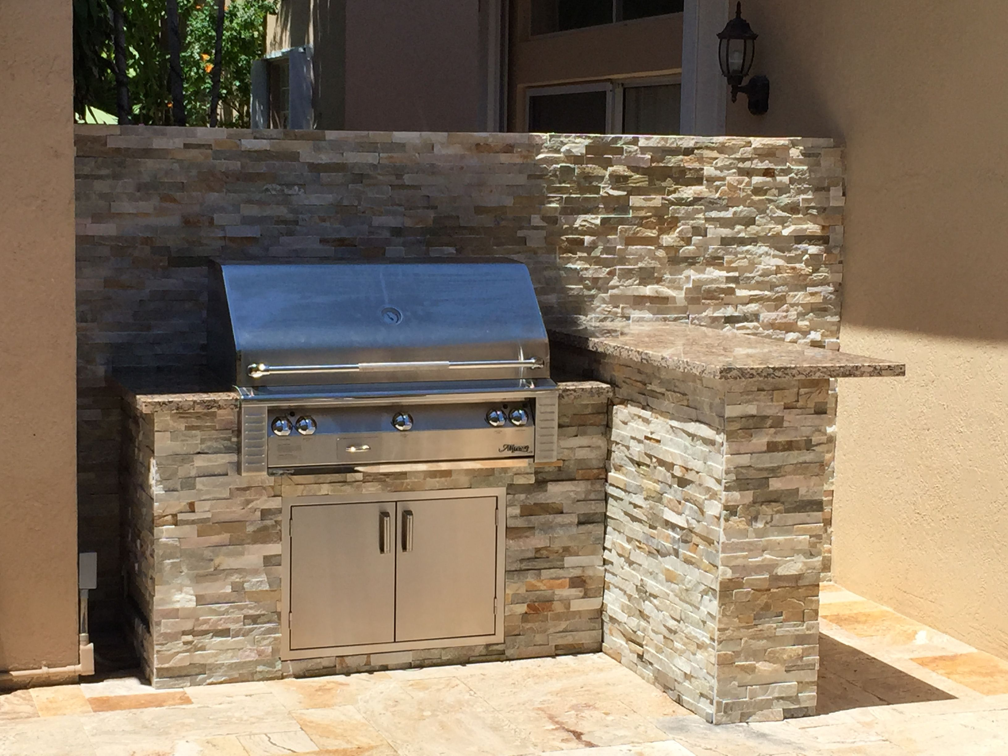 Small l shaped island with alfresco grill and rock finish