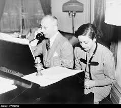Jerome Kern (1885-1945), talking on the telephone while his lyricist, Dorothy Fields (1905-1974), works at the piano, 1945.