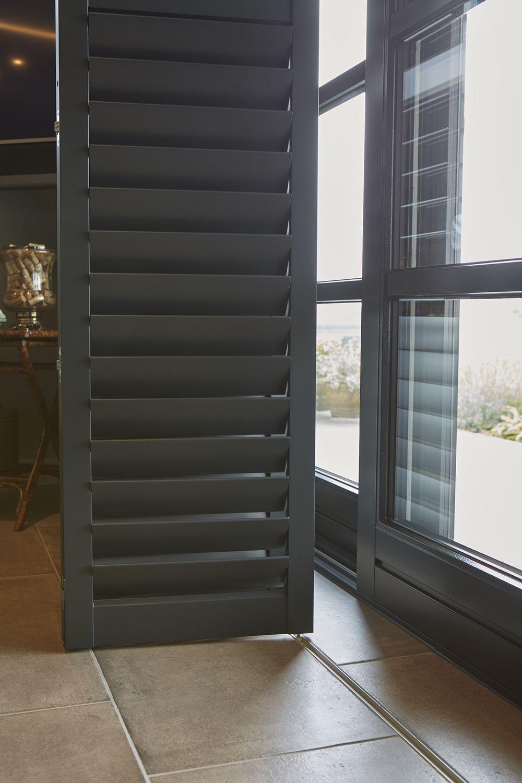 Voor De Schuifpuien Hangen Shutters Met Vouwrailsysteem De Zwarte Shutters Voor De Deuren Zorgen Voor Een Warme Sfeer Raambekleding Raamdecoratie Witte Keuken