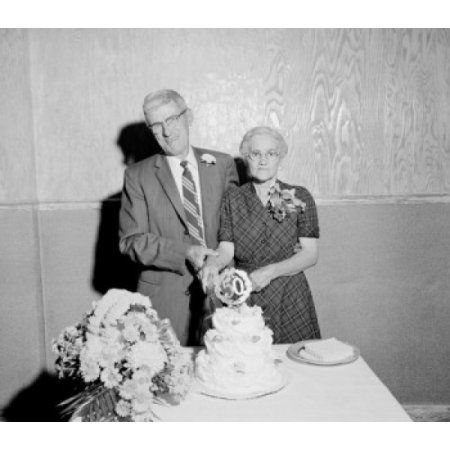 Portrait of senior couple cutting 50th wedding anniversary cake Canvas Art - (18 x 24)
