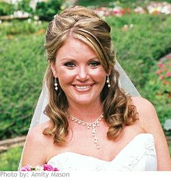 Hair is curled and pinned back into a half-up style. The bride's hair is also given some volume in the front and mid-section to securely fasten her veil.