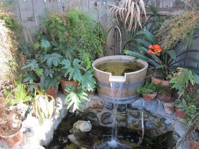 brunnen wasserspiele im garten deko holz fass teich pflanzen