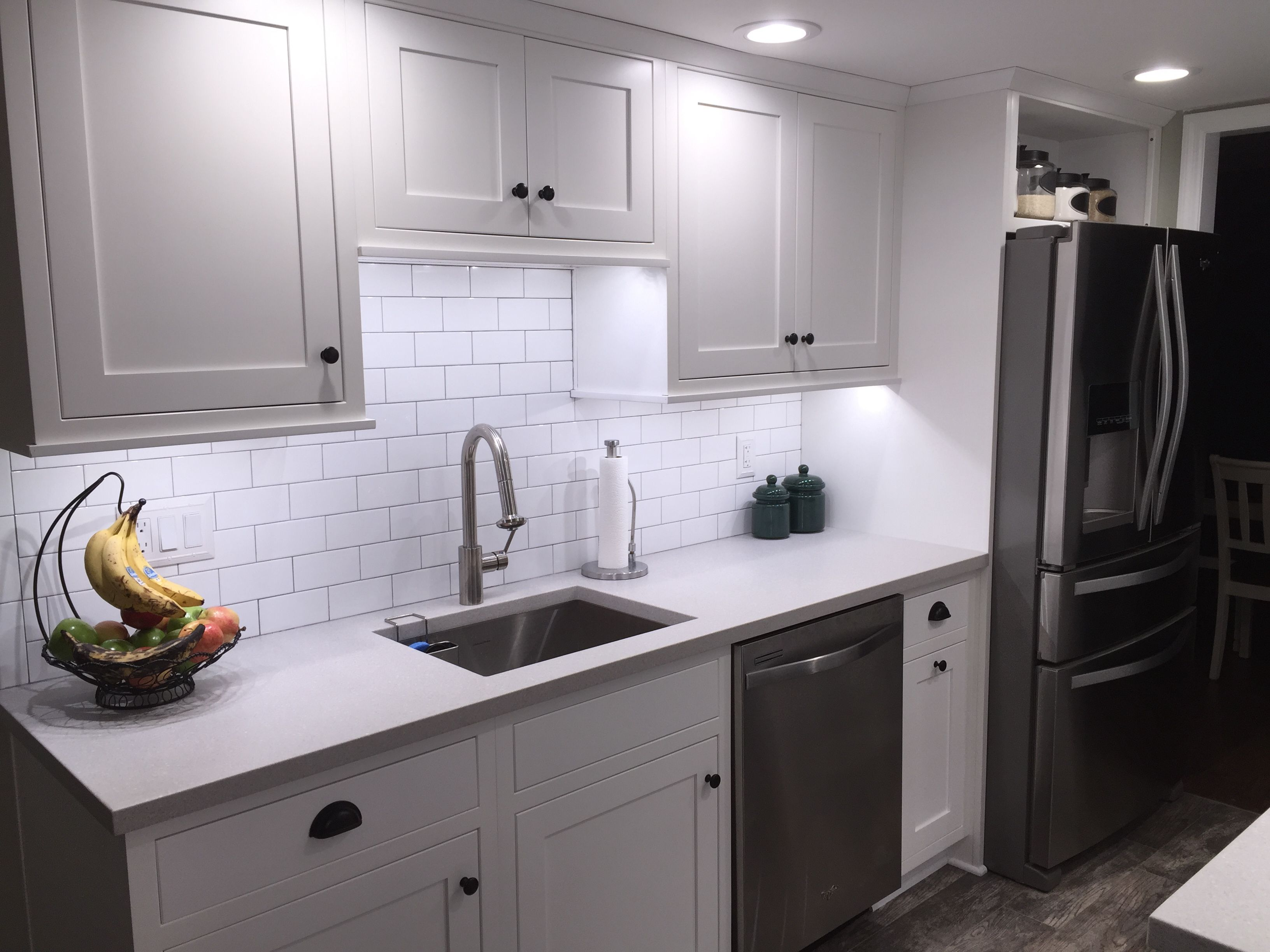 Galley Kitchen With White Shaker Cabinets Subway Tiles Faux Wood