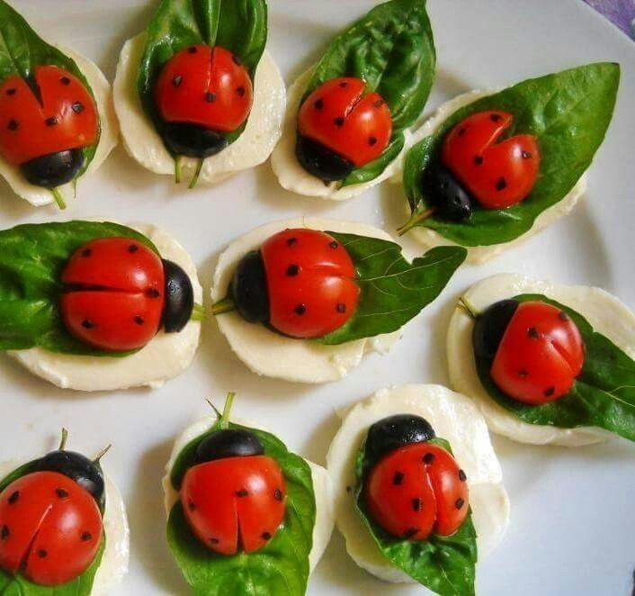 Ladybug caprese bites with mozzarella base, basil leaves, split cherry tomato with balsalmic dots, and black olive head.