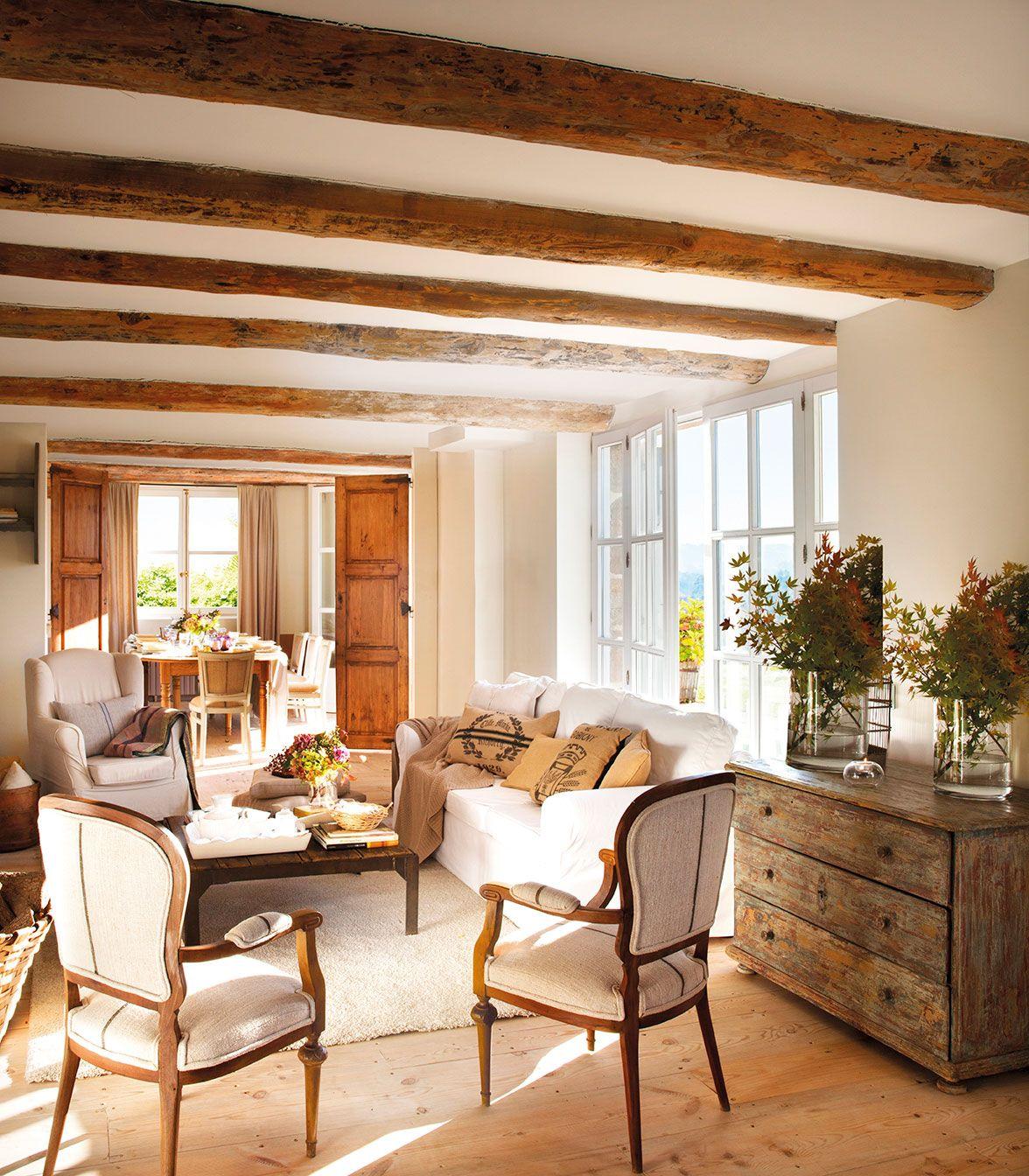 Sal n r stico con vigas de madera en el techo y sof s y for Como aislar el techo de un piso