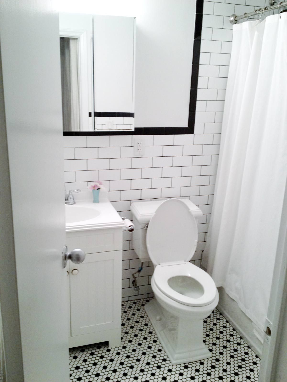 White subway wall tiles with black grout, black bullnose floor tiles ...